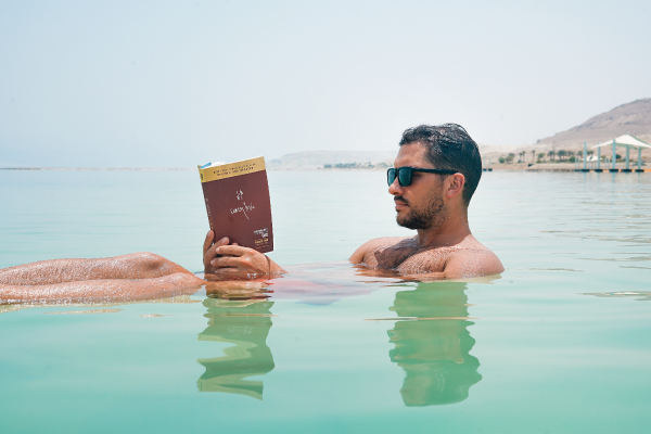 man floating in sea reading book
