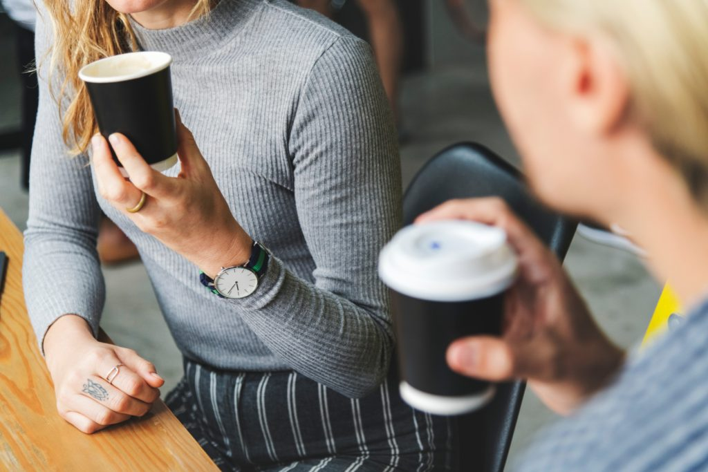 Image shows two women having a conversation over coffee.