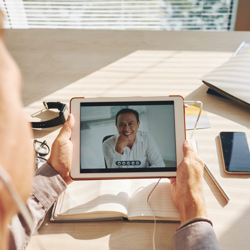 Businessman video conferencing with leader on digital tablet at desk in office