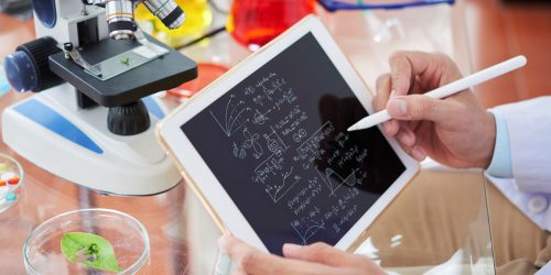 Scientist drawing chemical formulas and making calculations on tablet computer