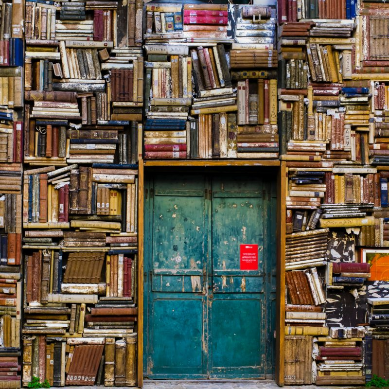 green door surrounded by book shelves