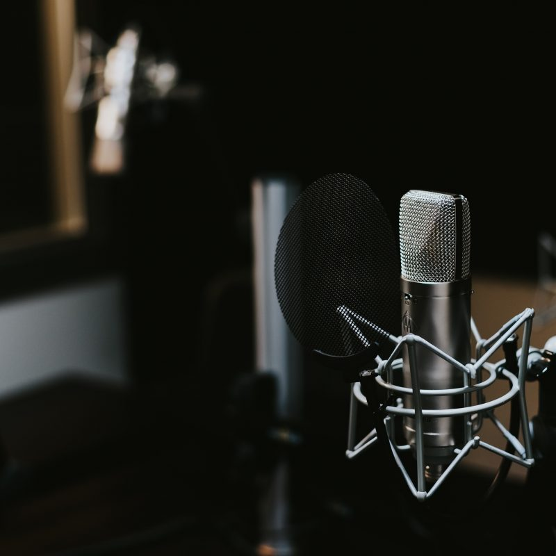 Image shows academic podcast equipment setup with microphone.